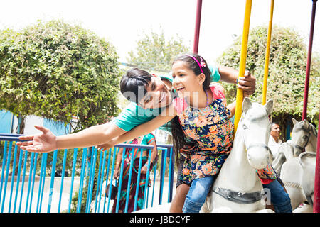2 Indian Father And Kid Daughter Fair Horse Ride having Fun - Stock Photo