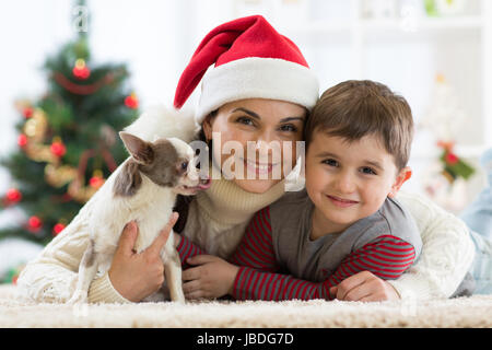Portrait of a happy family and the dog spending together Christmas time at home near the x-mas tree - Stock Photo