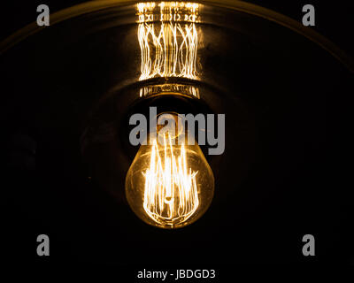 An old fashioned lightbulb illuminates in the darkness - Stock Photo