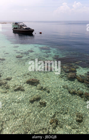 SIPADAN, BORNEO, MALAYSIA - A boat floating in front of coral reef. - Stock Photo
