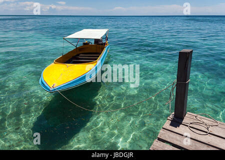 SIPADAN ISLAND, BORNEO, MALAYSIA - Colourful boat floating in calm crystal clear water. - Stock Photo