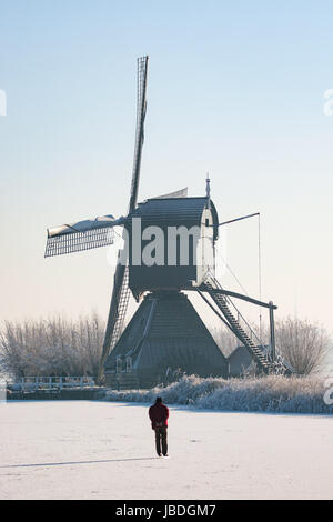 KINDERDIJK, THE NETHERLANDS - A dutch winter landscape with a person ice skating on natural ice in front of a dutch - Stock Photo