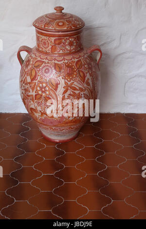 One large Tonala style Mexican hand-painted orange-red  2-handled jar against a white wall on a brown tiled floor, - Stock Photo