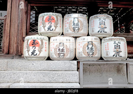 Empty Sake barrels ornament the front of a Shinto shrine in Japan, a cultural tradition believed to connect the - Stock Photo
