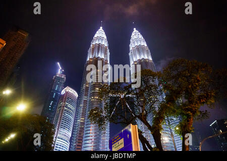 Kuala Lumpur, Malaysia - 5th May 2017: Petronas twin towers on a rainy night with a cloudy sky and pouring rain. - Stock Photo