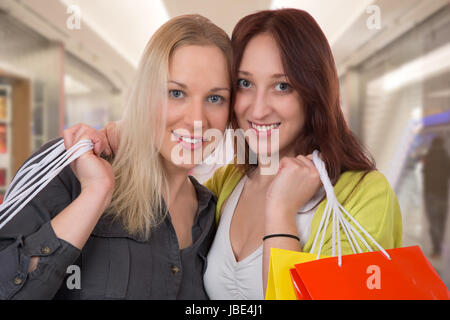 Zwei Freundinnen haben Spaß beim Einkaufen in einer Shopping Mall - Stock Photo