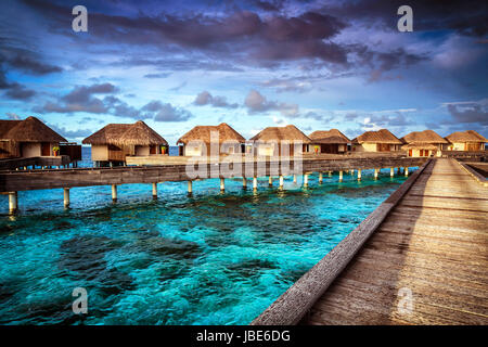 Luxury resort, many cute bungalow on the water, amazing view, beautiful coral under transparent water, summer holidays - Stock Photo