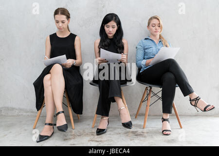 Group of asian and multiethnic business people with casual suit in queue waiting for job interview in modern office. - Stock Photo