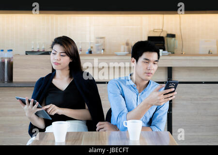 Asian couple looking at their mobile phone while on a date in cafe. Young Asian couple sitting and using their smartphones - Stock Photo
