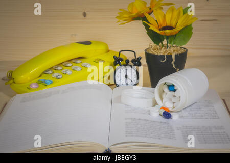 Medicine, Books, Sunflower in a Flowerpot and Alarm Clock, Telephone On a wooden background