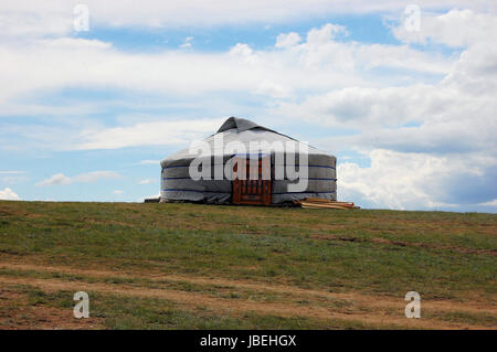 Traditional yurt tent home ger of Mongolian nomads on the grass plains of the steppe with colorful rolling hills - Stock Photo