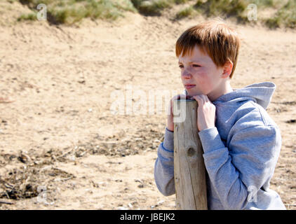 Young boy, leaning on a post and gazing into the distance at the beach. Taken in Lytham Saint Annes, United Kingdom - Stock Photo