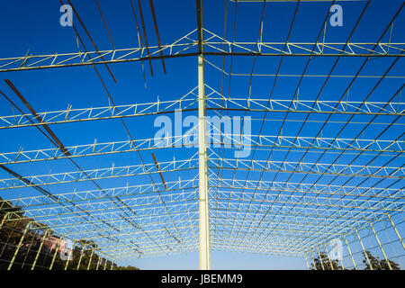 Steel frame warehouse building structure being put together piece by piece - Stock Photo