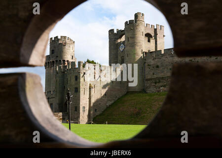 Barbican battlements, front, with the taller Gatehouse / Gate House in the background, seen through wooden stocks. - Stock Photo