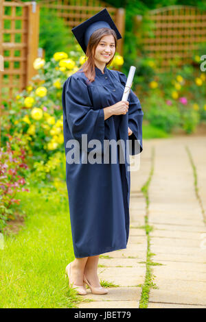 Smiling young woman holding diploma and wearing cap and gown outdoors looking at camera. Graduation concept. - Stock Photo