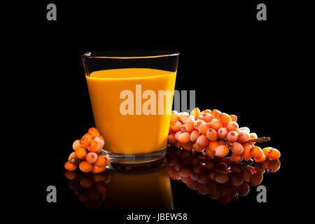 Sea buckthorn juice and berries isolated on black background. Alternative medicine. - Stock Photo