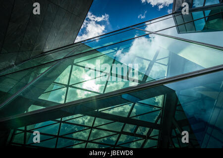Underside panoramic and perspective view to steel blue glass high rise building with reflections, skyscrapers, industrial - Stock Photo