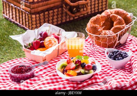 Healthy vegetarian or vegan picnic with a delicious spread of fresh fruit, golden croissants, berry jam and tropical - Stock Photo