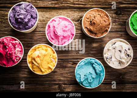 Selection of gourmet flavours of Italian ice cream in vibrant colors served in individual plastic tubs on an old - Stock Photo
