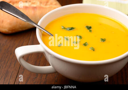 Hokkaido pumpkin cream soup on a kitchen table - Stock Photo