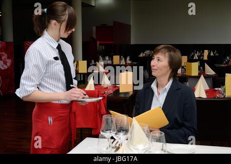 junge Restaurantfachfrau nimmt am Tisch beim Gast Bestellung auf - Stock Photo