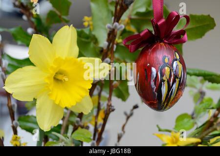 Osterglocke und kuenstlerisch bemaltes Osterei im Osterstrauss - Stock Photo