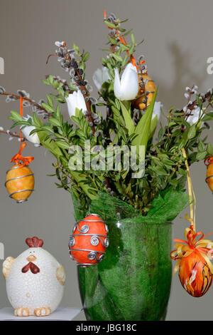 Osterdekoration mit buntem Osterstrauss, selbstgestalteten Ostereiern und Osterfigur - Stock Photo