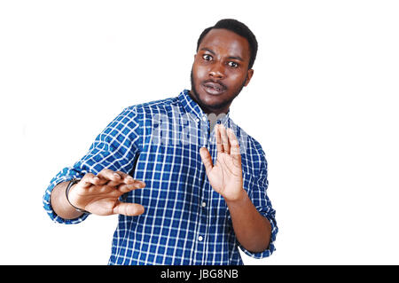 A scared looking young black man in a blue shirt with his arm's raised standing isolated for white background. - Stock Photo