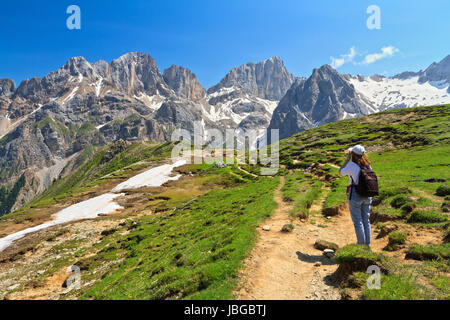 hiker on footpath  in Contrin Valley, Trentino, Italy. On background mount Marmolada - Stock Photo