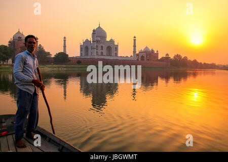 Local man steering boat on Yamuna river at sunset in front of Taj Mahal, Agra, India. It was build in 1632 by Emperor - Stock Photo