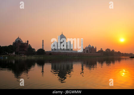 Taj Mahal reflected in Yamuna river at sunset in Agra, India. It was commissioned in 1632 by the Mughal emperor - Stock Photo