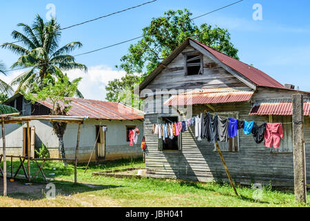 Livingston, Guatemala - August 31, 2016: Laundry hangs on washing line outside wooden house in Caribbean town of - Stock Photo