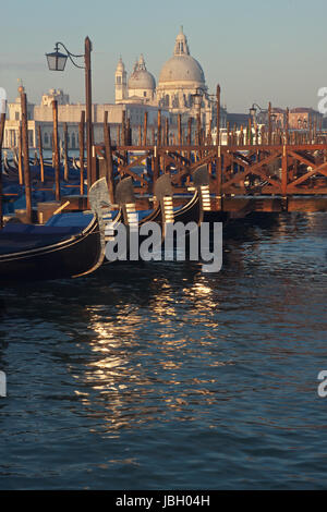 Venice, Italy - Gondolas parked on Grand Canal and Santa Maria Della Salute church on background - Stock Photo