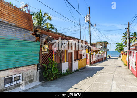 Livingston, Guatemala - August 31, 2016: Street leads down to water's edge in early afternoon in Caribbean town - Stock Photo