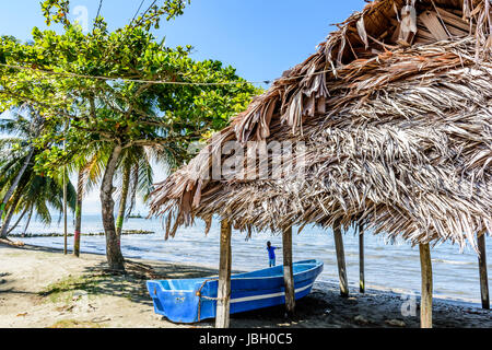 Livingston, Guatemala - August 31, 2016: Boat pulled ashore next to palapa on beach in Caribbean town of Livingston - Stock Photo