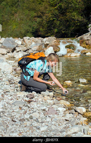 Hiker with backpack filling bottle of water - Stock Photo