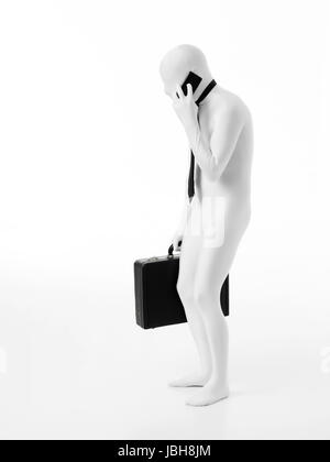 Hunched faceless businessman dressed in white, wearing tie, holding black briefcase talking on the phone - Stock Photo