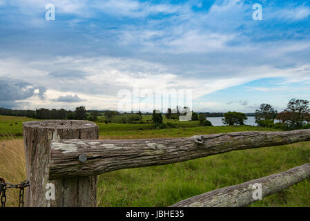 An old worn country post and rail timber fence and a distant river scene in rural New South Wales, Australia - Stock Photo