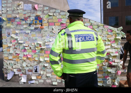 London UK. 11th June 2017. Police officers view the messages of condolence on a wall in London Bridge . It has been - Stock Photo