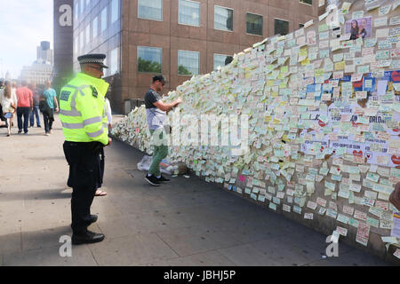 Police officers view the messages of condolence on a wall in London Bridge . It has been  a week since the London - Stock Photo