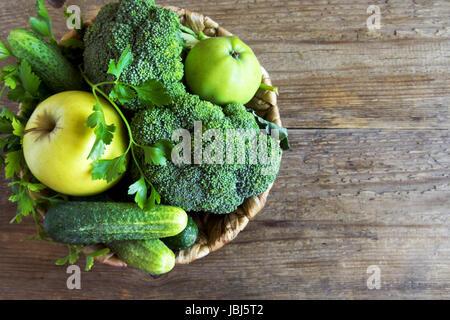 Vegetables . Assorted Organic Harvest Green Vegetables in a Basket. Fresh Vegetables over rustic wooden background. - Stock Photo