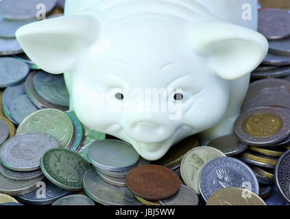 white piggy bank  isolated on white background with coins - Stock Photo