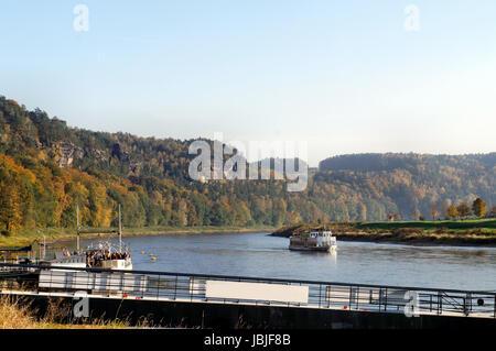 Die Elbe im deutschen Teil des Elbsandsteingebirges; steile Felsen und bunte Laubwälder; auf dem Fluss ein Dampfer - Stock Photo