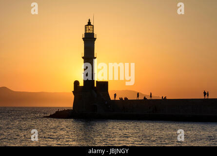 Chania, Crete sunset silhouette over the lighthouse at the entrance to the Venetian harbour wall of Hania, Crete, - Stock Photo