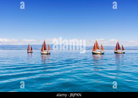 Traditional sailing boats on Lake Geneva, off the shore of Évian-les-Bains, France - Stock Photo