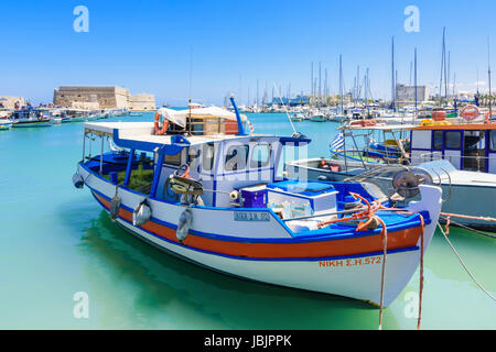 Fishing boats moored in the inner harbour with the Koules Fortress in the background, Heraklion, Crete, Greece - Stock Photo
