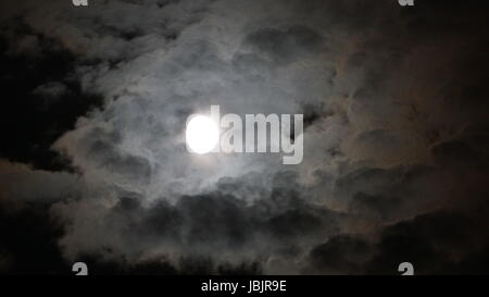 Full moon behind clouds at night . black background - Stock Photo
