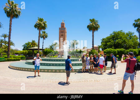 Marrakech, Morocco -  May 12, 2017: A group of tourists taking photos of each other in front of the fountain in - Stock Photo