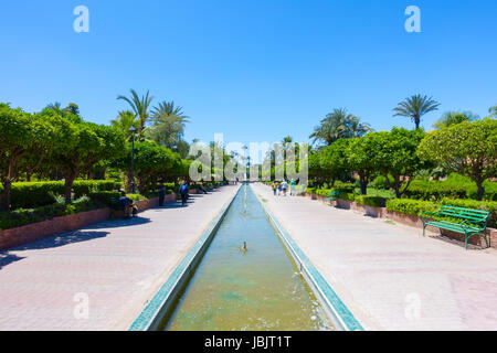 Marrakesh, Morocco - May 12, 2017: Tourists and locals are relaxing on a sunny day in the Koutoubia Gardens. - Stock Photo