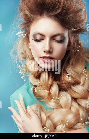 Enjoyment. Woman with Plait and Intertwined Flowers - Stock Photo